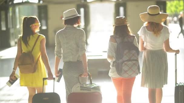 Zadní pohled na čtyři docela dobře vypadající dívky s dokumenty, jízdenky a velké cestovní tašky v rukou na letišti. Letní prázdniny, cestování koncepce.