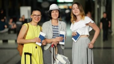 Amazing Smiling Girls in Bright Summer Clothing are Happy to Have Vacation Together. Young Women are Holding Documents and Tickets in Hands While Waiting at the Airport.