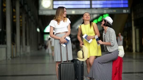 Legrační kamarádky jsou čekající spolu letadlo na letišti. Portrét tří smějící se žen s dokumenty, cestovní tašky a lístky v rukou.