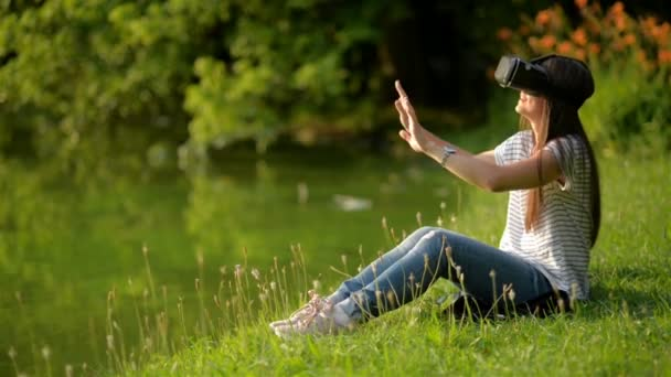 Portrait of Young Woman with Virtual Reality Goggles Sitting Near the Lake in the City Park. Amazing Brunette is Using Head-mounted Display Outdoors.