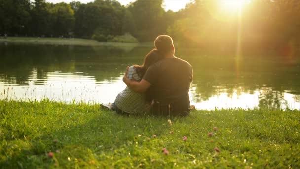 Pohledný muž se objímají jeho přítelkyně sedí u jezera v City parku během krásný západ slunce. Zadní pohled na šťastný pár mimo.
