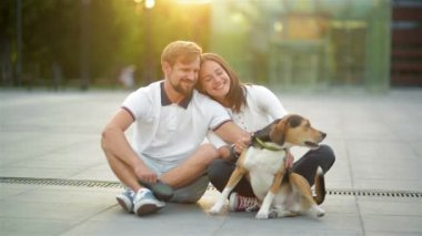 Outdoors Portrait of Couple in Love Enjoying Summer Sunset with Beagle Dog Sitting on the City Square.