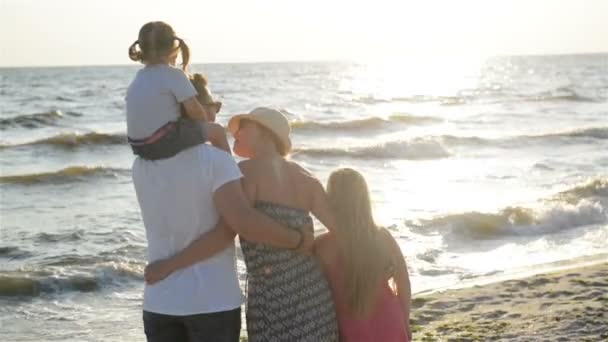 Handsome Father and Attractive Mother with Two Daughters Spending Time Together near the Sea During Sunset. Man Holding One Child on His Shoulders.