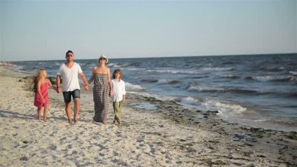 Čelní pohled čtyřčlenná rodina chůzi na pláži během letní dovolené u moře.