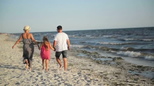 Back View of Happy Family with Little Daughter Walking on the Beach Holding Hands During Summer Vacation on the Seaside.