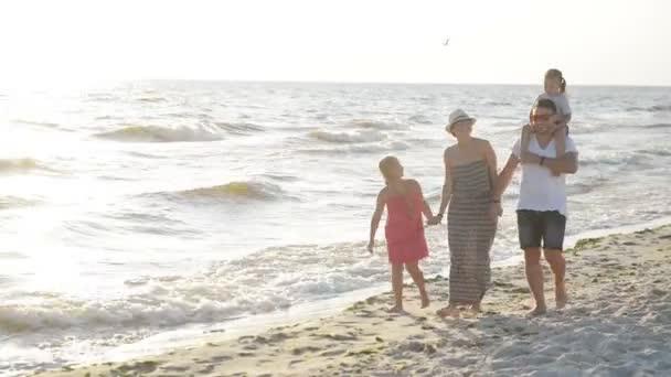 Nám s úsměvem rodina chůzi spolu poblíž moře během slunečného letního dne. Krásný pár s dvěma dětmi trávit čas u moře.