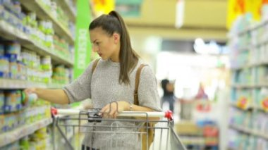 Front View of Amazing Young Woman with Shopping Cart Buying Healthy Baby Food in the Hypermarket Standing Near Shelf With Goods.