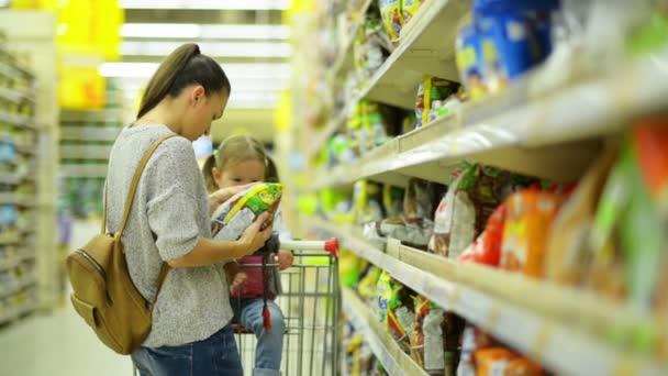 Krásná bruneta žena s roztomilý dívka stojící poblíž police s zboží vypadá pečlivě na každém produkty držet v ruce