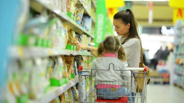 Boční pohled na krásná bruneta žena s roztomilá holčička stojí poblíž police zboží. Šťastná rodina výběr výrobků v hypermarketu