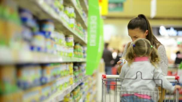 Rodinný koncept nákupu. Portrét usmívající se žena a dívka vybrat výrobky v prodejně potravin