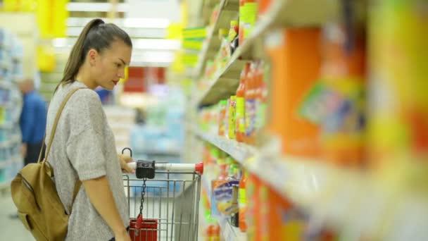 Úžasná mladá bruneta žena s nákupní košík nákup některých nápojů v hypermarketu, stojící poblíž police s džusy