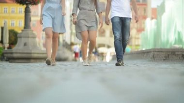 Three Friends Are Walking on Pavement at Midday. They Are Having Fun at This Sunny and Heat Weather.
