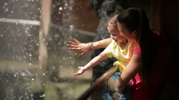 Mother and Cutie Daughter Playing With Small Waterfall. They Are Having a Lot of Fun at Mothers Day Together.