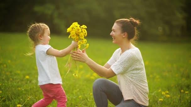 Veselá dcera dárky kytice k matce. Krásná mladá matka všeobjímající její roztomilý dcera s žluté zářivé květy v létě pozadí.