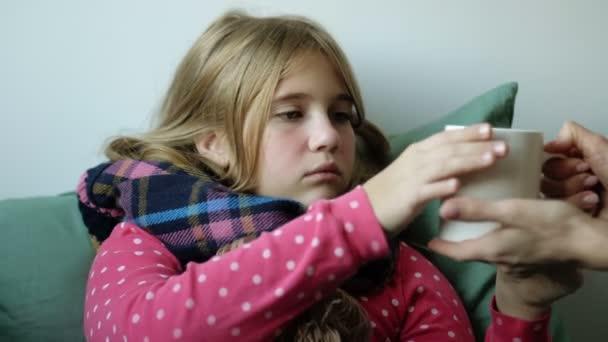 Nemocná holčička s nachlazením sedí v posteli pod přikrývkou se skarfem a pije horký bylinkový čaj. Pečující matka dává své dceři teplý nápoj