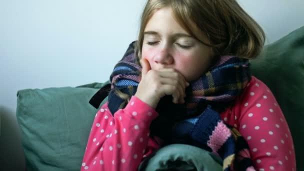 Domácí péče. Holka se šálou je doma nemocná, má rýmu a chřipku. Teplě oblečená a přikrytá přikrývkou. Vysmrká se do ubrousku. Infekce, epidemie