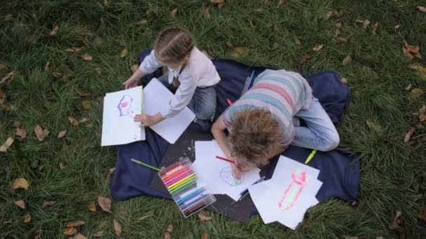 Two cheerful kids, boy and girl lying on green grass in summer park. Children siblings are reads draws, plays, laughs.