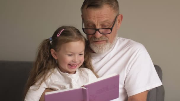 Grandfather teaches his granddaughter to read books. Family educational concept. An elderly man and a little girl leaf through a textbook