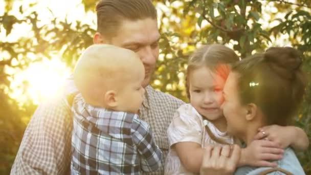 Boldog apa átöleli a családját egy parkban egy napsütéses napon. Anya, apa és a gyerekek nevetnek és ölelkeznek naplementekor a parkban..