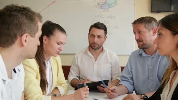 Corporate Business Team Arbeitstreffen im Büro. Fünf kaukasische Geschäftsleute und Geschäftsfrauen sprechen gemeinsam über Strategie. Zusammenarbeit, Wachstum, Erfolgskonzept mit Diagramm.
