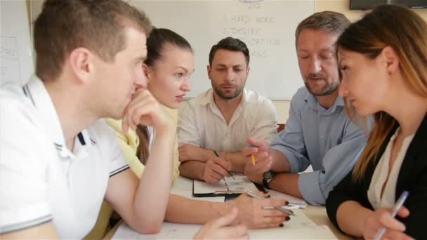 A Team Of Office Employees Discussing On A Creative Project In Boardroom. A group Of Young Member Of Staff Working Together And Planning On An Important Assignment In Modern Caucasian Start Up Office.