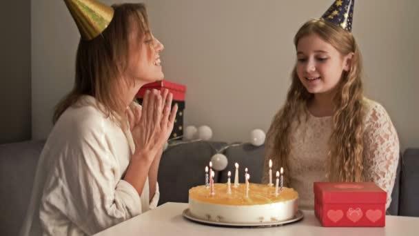 Gyönyörű anya és tinédzser lánya ünneplik a születésnapjukat. Anya és a gyerek gyertyákat fújnak a tortára.