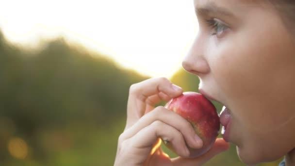 Gyermek lány bio almát eszik a kertben. Aratási koncepció. Közelről.