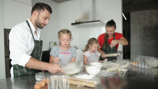 Family of four sculpts dumplings in the kitchen. Children help parents.