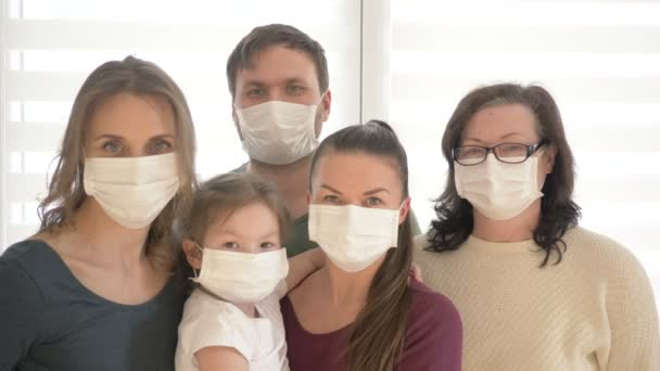 Family of five wears a protective medical mask to prevent coronavirus. Adults and children in medical masks to prevent disease
