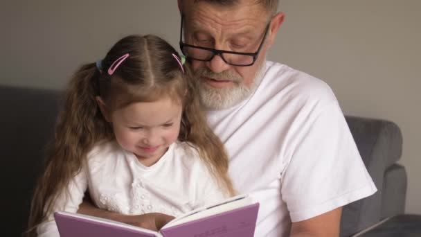 Portrait shot of the grandfather in glasses and cute teen granddaughter reading a book together while sitting on the sofa at home