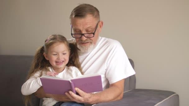 Der Großvater lehrt seine Enkelin Bücher lesen. Familienbildungskonzept. Ein älterer Mann und ein kleines Mädchen blättern in einem Lehrbuch