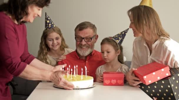 Nagy, barátságos, többgenerációs család áll együtt otthon, és nézik, ahogy nagyapa gyertyákat fúj a szülinapi tortán..