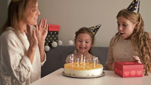 Mosolygó anya és lánya elfújja gyertyák születésnapi torta otthon, család és ünneplés koncepció