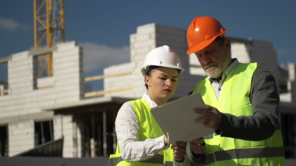 Muž a mladá žena v přilbách na pozadí domu ve výstavbě.