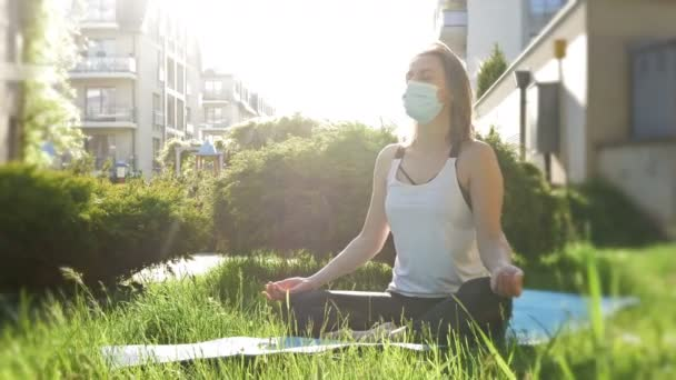 Woman in a medical mask practices yoga in the courtyard of her house. Concept of healthy lifestyle, wellness, being safe while coronavirus pandemic.