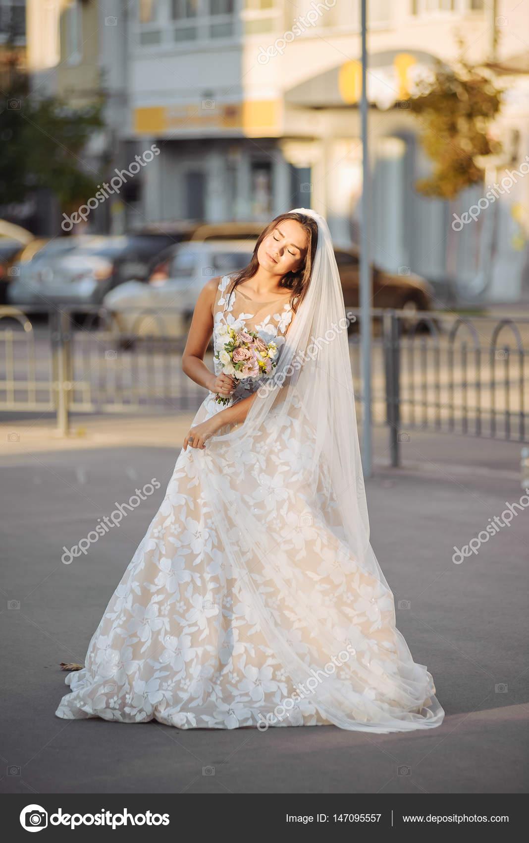 Bella novia en pose sexy con flores al aire libre. Ella Mostrar ...