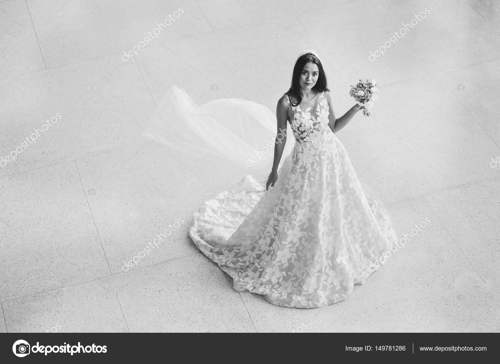 Schöne Braut in sexy Pose mit Blumen im Freien. Sie zeigen ...