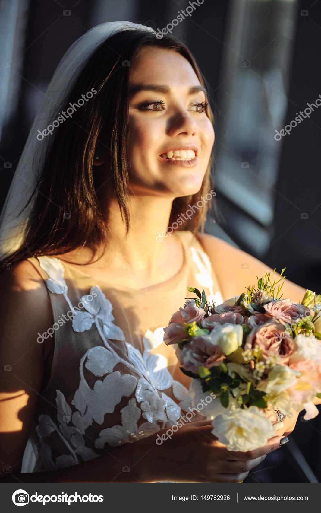 Schöne Braut mit Blumen im Freien. Sie zeigen erstaunliche Lächeln ...