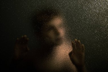 Scary Young Boy Leaning Against a Textured Glass