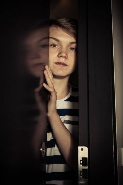 Teenager boy behind ajar door