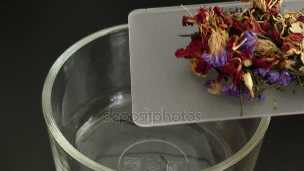 Mixing dry flowers herbal tea transparent glass closeup