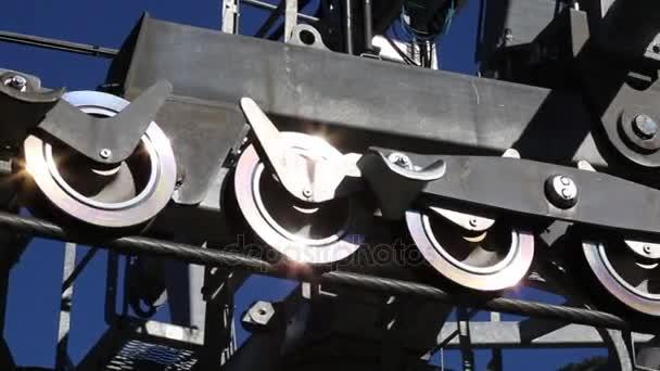 Mechanic moving shiny gear wheels gondola lift closeup