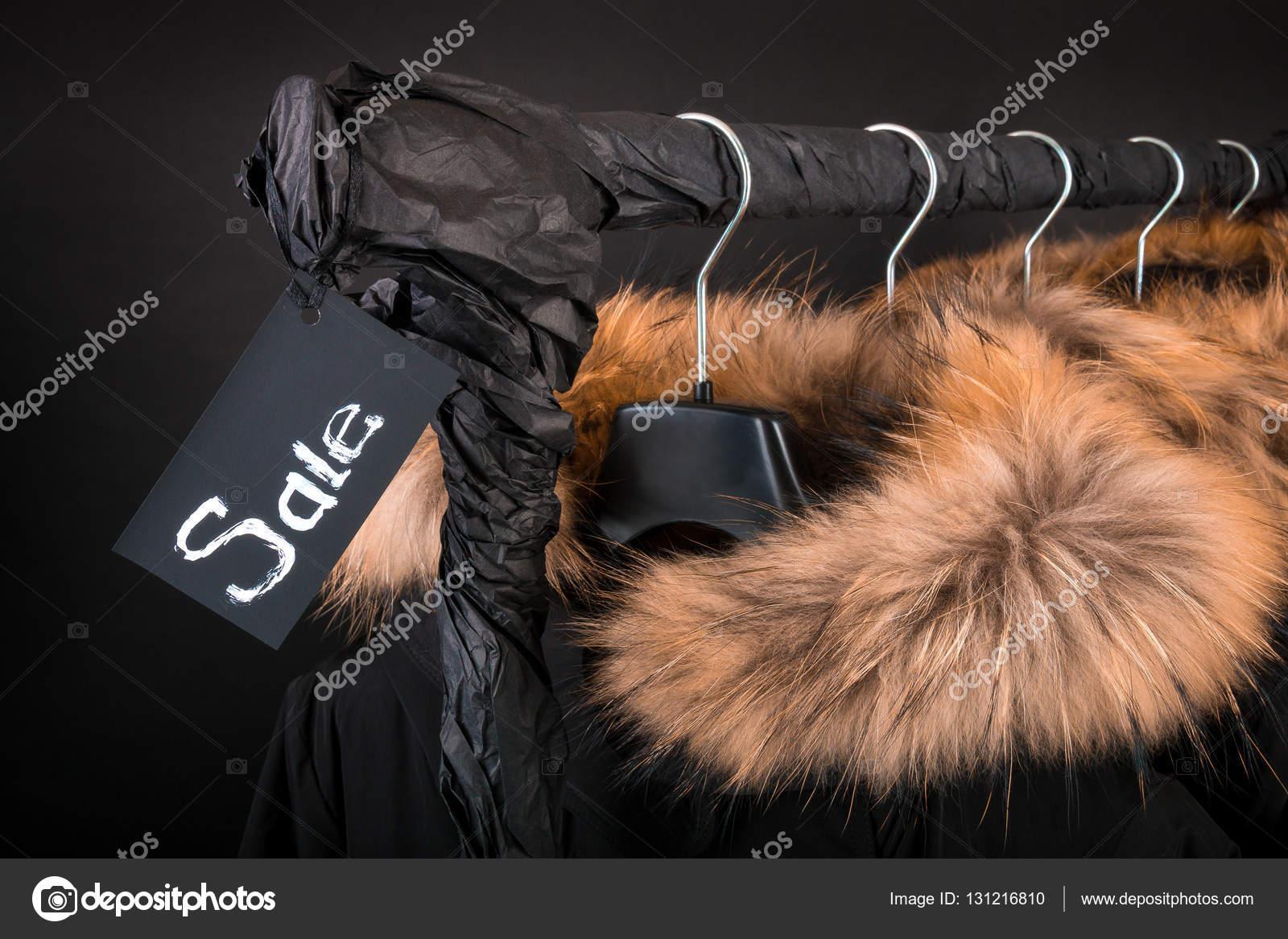 af32a2665655 Schwarzer Freitag. Viele schwarze Mäntel, Jacke mit Fell Kapuze  Kleiderständer hängen — Stockfoto