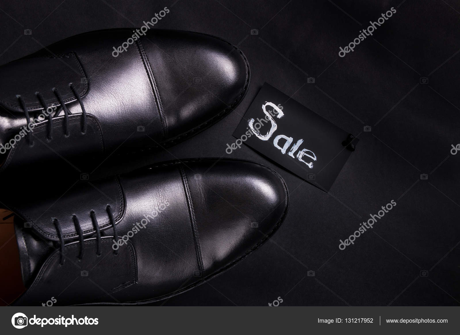 Sale sign. Black oxford shoes on
