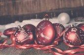 Červené vánoční koule a stuhy na dřevěné pozadí. Novoroční přání. Rám. Kopírovat prostoru. Tónovaný fotografie