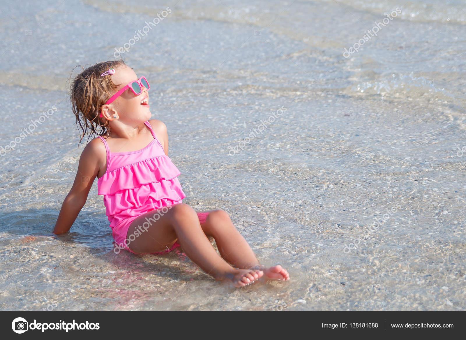 Costumi Da Bagno Per Bambino : Bambino in costume da bagno rosa e occhiali da sole che si siede