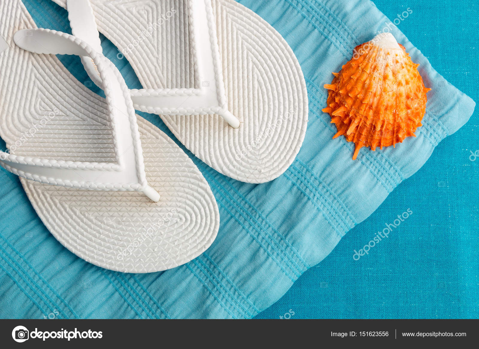 1c782d5cd White flip flop near seashell on blue background. Top view. — Stock Photo