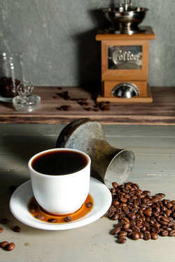 A White Cup of Hot Coffee in a Scattering of Coffee Beans on a Wooden Background