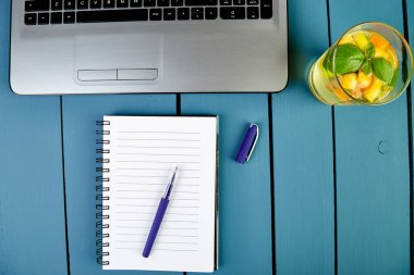Modern women workplace with notebook or laptop, detox water or lemonade. Still life, business, office supplies or education concept. Flat lay. Top view.