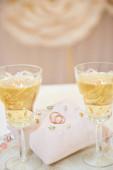 zwei Gläser Champagner und Kissen mit Eheringen